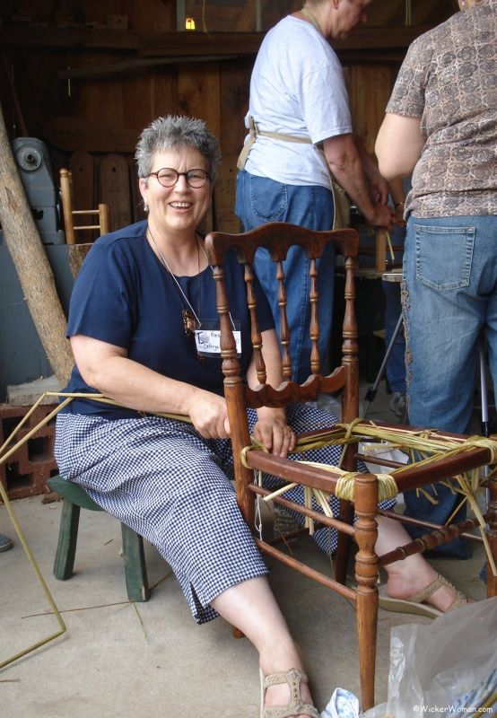 Cathryn Peters demonstrating weaving a hand-twisted cattail chair seat