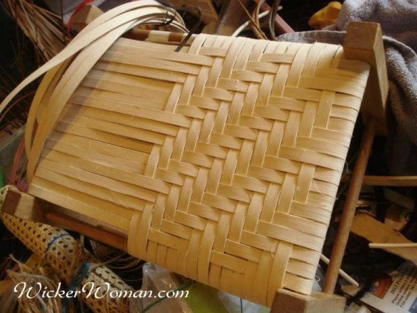 Woven reed footstool in process